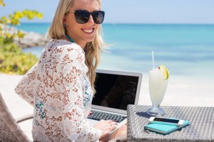 Woman working abroad on beach with laptop